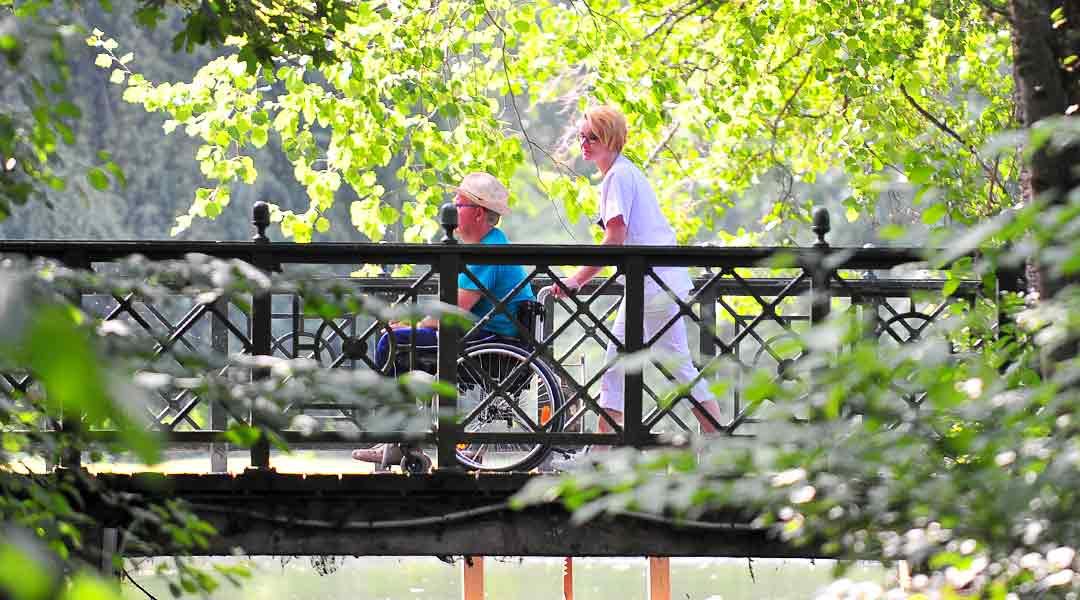 Patient mit Pflegekraft beim Spaziergang im Park