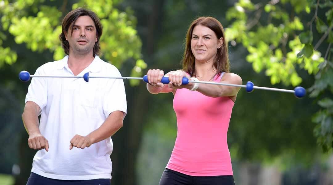 Physiotherapeutische Übung mit dem Schwingstab im Park