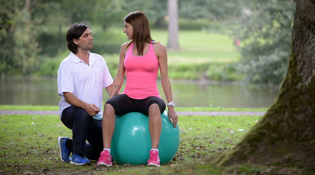 Physiotherapie Übung mit dem Gymnastikball im Park
