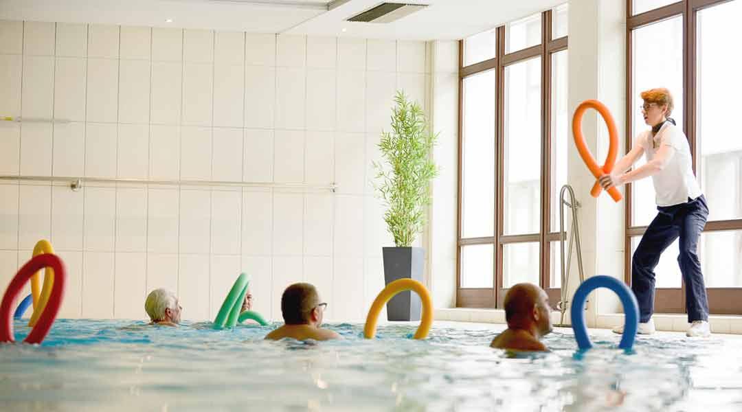Sporttherapie Trainerin gibt Kurse im Bewegungsbad mit Poolnudel