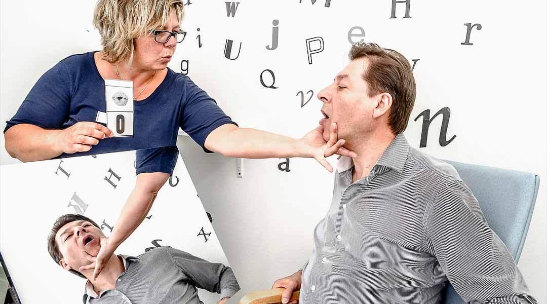 Sprachtherapie Pflegerin übt mit Patient den Buchstaben-O-zu sprechen
